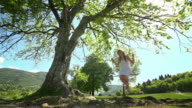Girl in white dress swinging on rope swing under tree video