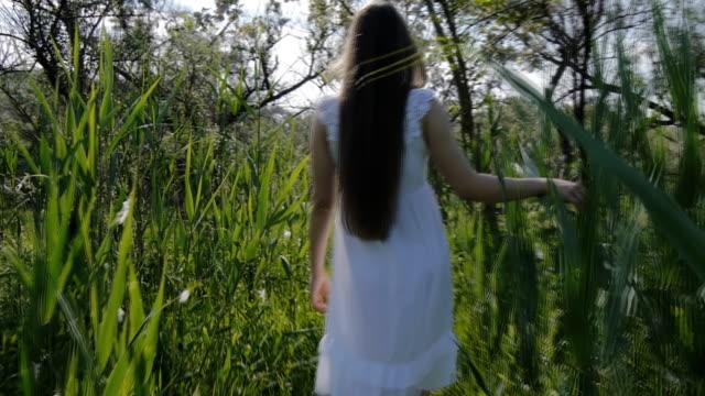 Girl in white dress walking through the grass video