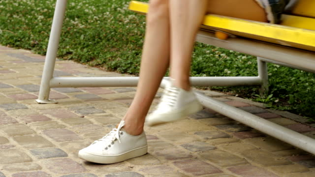 girl in white sneakers is sitting on a swing video
