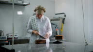Girl in white uniform neatly cuts the chocolate cake into three equal pieces in the kitchen at the bakery. Baker at work looking to the side video