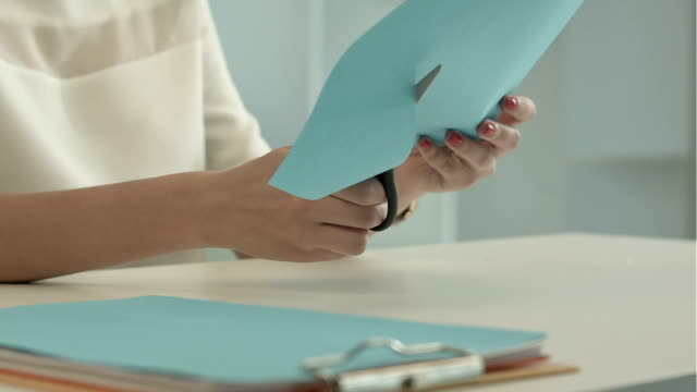 Girl is cutting color blue paper with scissors video