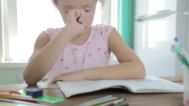 Girl is doing homework for elementary school. video