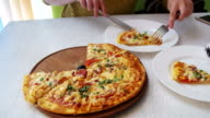 Girl is Eating a Pizza on a White Plate in a Restaurant at a White Wooden Table. Dolly Shot video