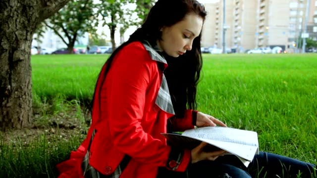 A Girl is Reading Sitting on the Grass. video