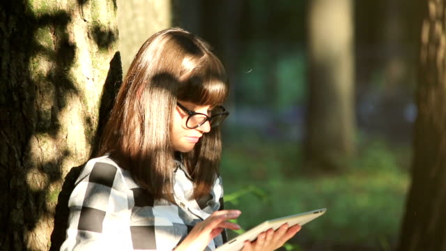 Girl is Relaxing in the Park with a Tablet PC video