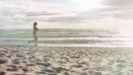 Girl is Running at Morning Time in Beach. Side Shot. video