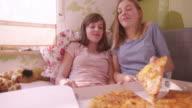 Girl joking and feeding her friend huge slice of pizza video