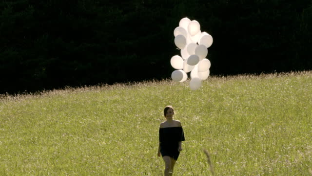 Girl jump with bunch of balloons in field summer time video