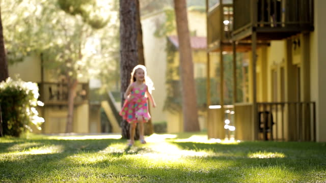 Girl jumping, dancing, spinning in an oak alley. The wind blew her hair and dress. Bright and sunny picture. Hair is covering the face.Fain art film. video