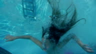 Girl jumping from springboard and diving in Swimming Pool. video