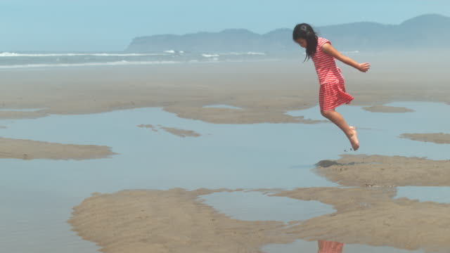 Girl jumping into puddle at beach, slow motion video