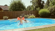 SLO MO CS Sister jumping into pool with younger brother video