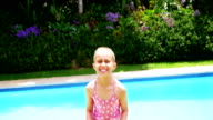 Girl jumping near swimming pool video