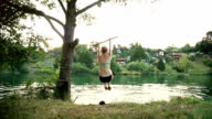 Girl jumping off rope swing into river video