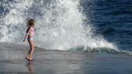 Girl jumping with big waves on the shore during a storm. video