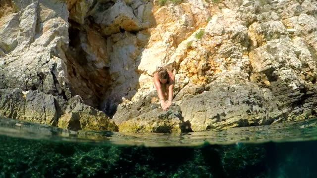 SLOW MOTION: Girl jumps head first into refreshing ocean and swims under camera video