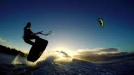 Girl Kite Surfing Catches Air Over Ocean Wave in Bikini. Extreme Kitesurfing Girl at Sunset. video