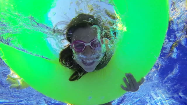 Girl laughing underwater in a swimming pool video