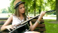 Girl learning how to play guitar outdoors video
