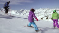 TS Little girl learning to ski on sunny day with parents video