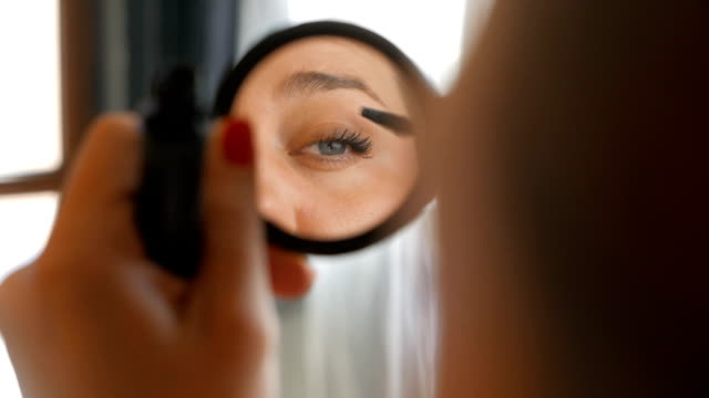 Girl looking at the mirror applying make up video