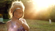 Girl looking through a magnifier at sunset video