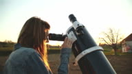 Girl looking through a telescope. video
