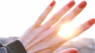 girl looks at the sun through the fingers of the first person video