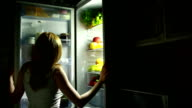 Girl looks in the fridge at night. night meal. Woman wants to eat video