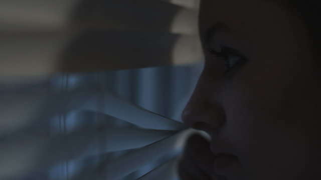 HD: Girl looks out of the blinds (Shot on RED) video