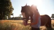 Girl lovingly rubbing her horse's mane in a field video