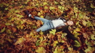 Girl lying down on dry leaves video