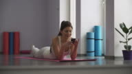 Girl lying on the yoga mat and looking at the phone video