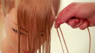 Girl makes a braid. Wizard makes the hair of the mannequin. White. Close up video