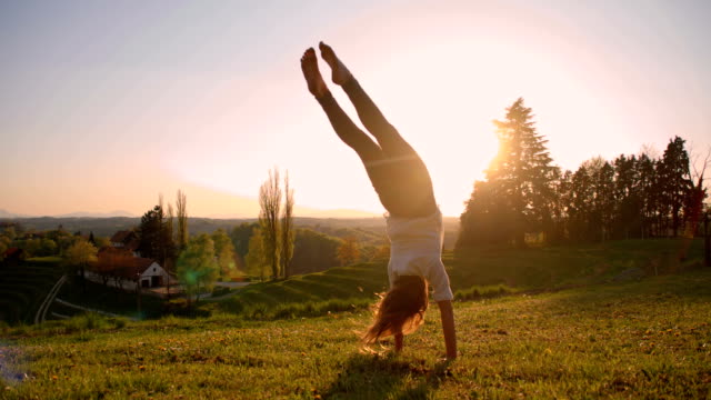 SLO MO Girl makes acrobatic move in meadow video