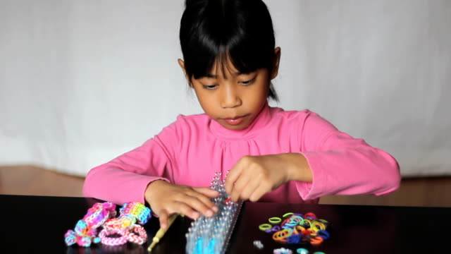 Girl Making Colorful Bracelet On Her Loom video