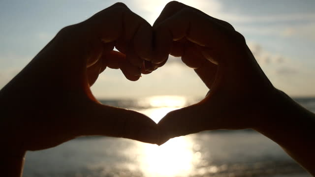 Girl making heart with her hands over sea background with beautiful golden sunset. Silhouette of female arm in heart shape with sunrise inside. Vacation concept. Summer holidays on beach. Slow motion video