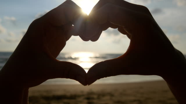 Girl making heart with her hands over sea background with beautiful golden sunset. Silhouette of female arm in heart shape with sunrise inside. Vacation concept. Summer holidays on beach video