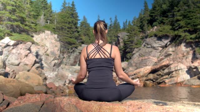 CLOSE UP: Girl meditating on rocky volcanic seashore facing small waterfall video