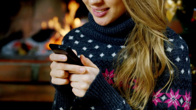 Girl near the fireplace with your smartphone video