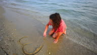 girl on beach drawing heart deleted by sea Stock Video video