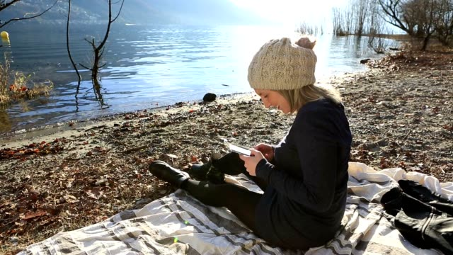 Girl on blanket at lake text messaging on smart phone video