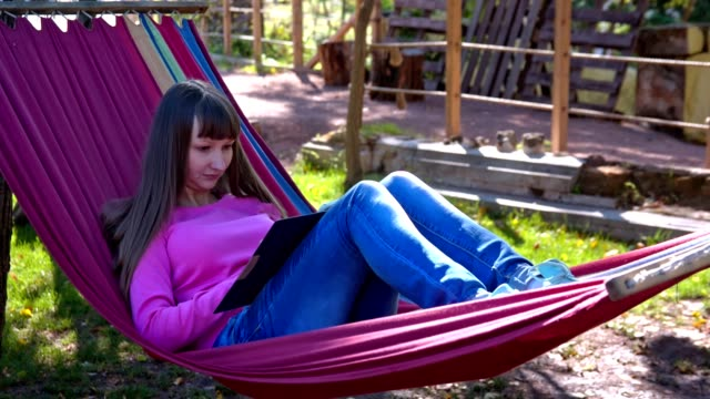Girl on hammock with tablet pc video