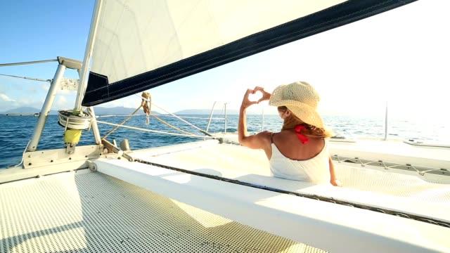 Girl on sailing boat makes heart shape finger frame video