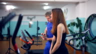 Girl on the exercise bike and a man with a clipboard in gym video