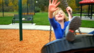 Girl on tire swing waves to the camera video