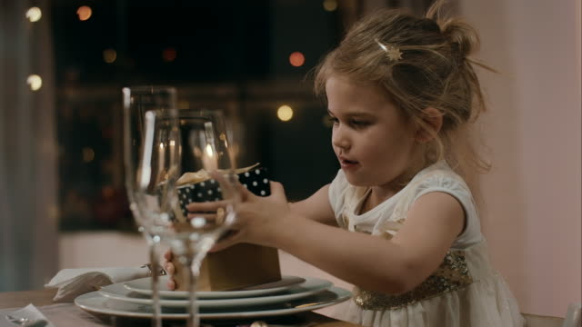 Girl opening present on dinner table video