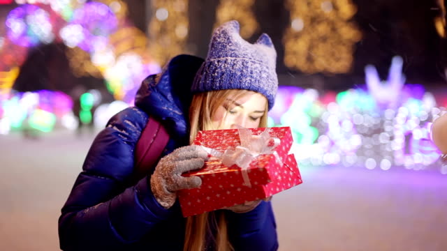 Girl opens a red gift box on street video