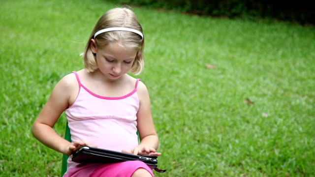 Girl outdoors using with tablet computer ipad video