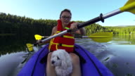 Girl paddling Kayak across a lake with pet dog video